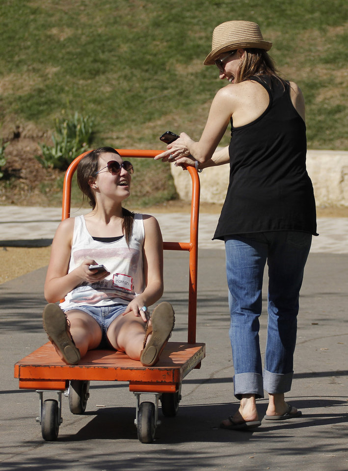 Hannah Holloway hitches a ride from her mother, Carmie Holloway during the last day of the Festival of the Arts, Sunday, April 28, 2013. The Holloways are volunteers. Photo by Doug Hoke, The Oklahoman