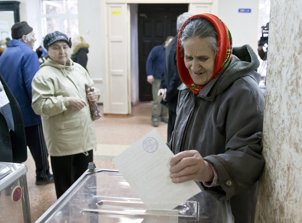 Photo - A woman casts her ballot in the Crimean referendum in Simferopol, Ukraine, Sunday, March 16, 2014. Residents of Ukraine's Crimea region are voting in a contentious referendum on whether to split off and seek annexation by Russia. (AP Photo/Vadim Ghirda)