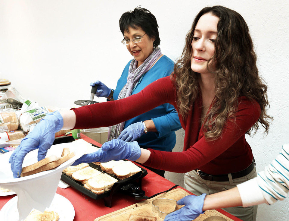"Nancy Smith, left, and Kimberly Minor make sandwiches for ""Art From the Heart"" attendees."