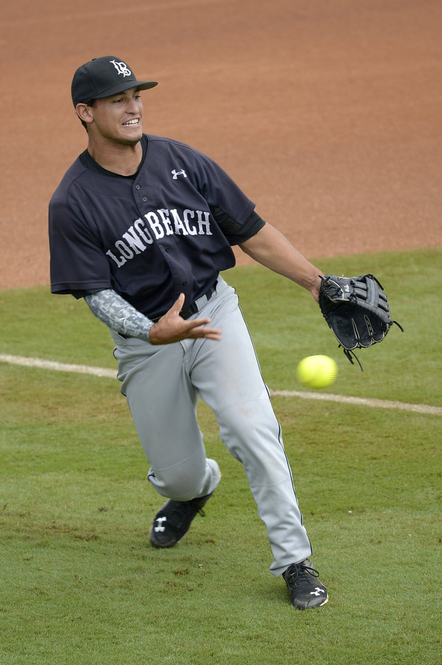 Photo - Long Beach State's Zack Rivera loosens up by throwing a softball during a rain delay in the fourth inning of an NCAA college baseball regional tournament game against North Carolina in Gainesville, Fla., Sunday, June 1, 2014. (AP Photo/Phelan M. Ebenhack)
