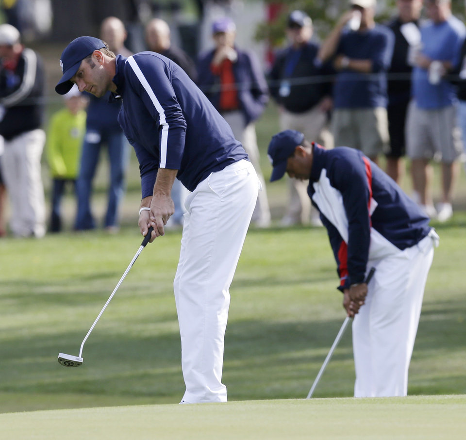Photo -   USA's Tiger Woods, right, and Dustin Johnson putt on the 15th hole during a practice round at the Ryder Cup PGA golf tournament Thursday, Sept. 27, 2012, at the Medinah Country Club in Medinah, Ill. (AP Photo/David J. Phillip)