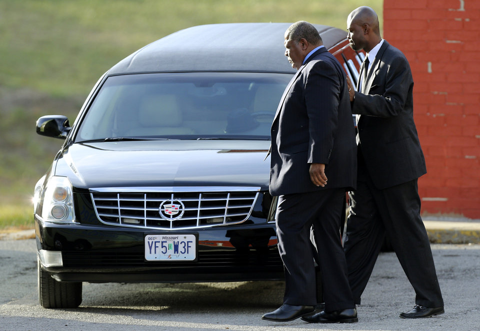 Photo - Kansas City Chiefs head coach Romeo Crennel, left, leaves a memorial service for Jovan Belcher at the Landmark International Deliverance and Worship Center, Wednesday, Dec. 5, 2012, in Kansas City, MoO. Belcher shot his girlfriend, Kasandra Perkins, at their home Saturday morning before driving to Arrowhead Stadium and turning the gun on himself. (AP Photo/Ed Zurga)