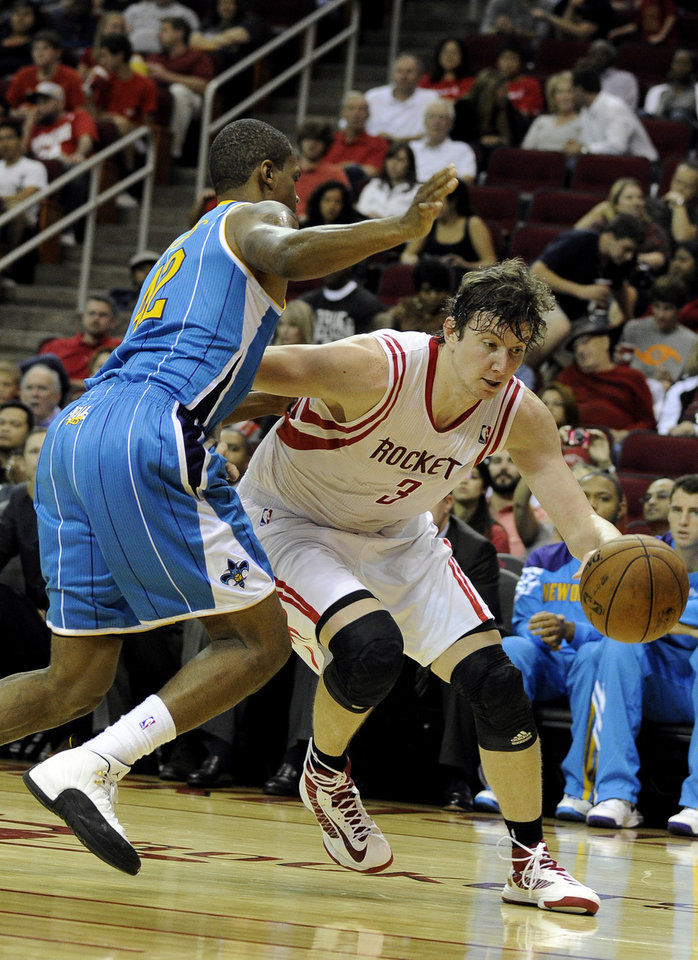 Houston Rockets' Omer Asik (3) drives the ball around New Orleans Hornets' Lance Thomas in the second half of a preseason NBA basketball game Friday, Oct. 12, 2012, in Houston. (AP Photo/Pat Sullivan)