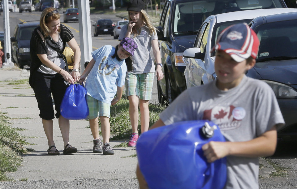 Photo - Mary Ellen Kavanaugh, and her children Abby, second from left, Grace and Owen, right, of Windsor, help carry water jugs to St. Peter's Episcopal Church in Detroit, Thursday, July 24, 2014, for a water station being set up to help Detroit residents who need water. A small group of Canadians brought 1,000 liters (264 gallons) of water from Windsor, Ontario, to Detroit to protest thousands of residential service shutoffs by Detroit's water department. (AP Photo)