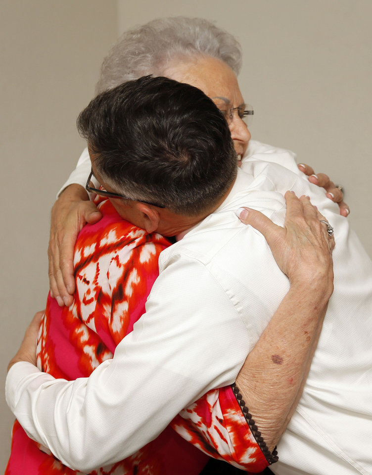Photo - Ruby Walker, 78, hugs her chiropractor, Gregory S. Howard, during an appointment at his office in Frederick, Okla. Walker was Howard's first patient when he began his practice in Frederick.  NATE BILLINGS - NATE BILLINGS