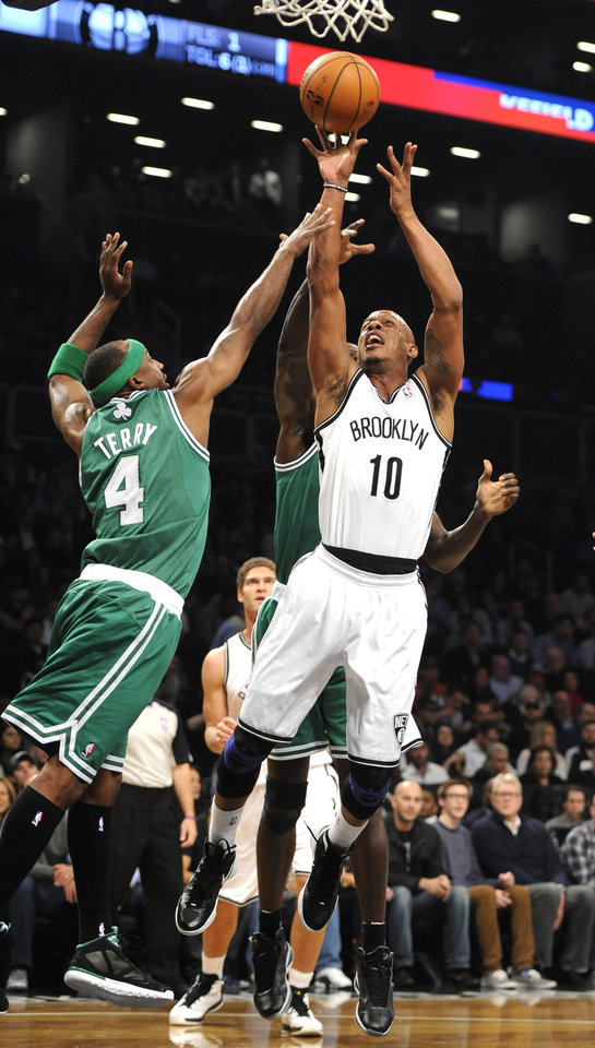 Brooklyn Nets' Keith Bogans (10) takes aim over Boston Celtics' Jason Terry (4) during the first half of an NBA basketball game on Thursday, Nov., 15, 2012, at Barclays Center in New York. (AP Photo/Kathy Kmonicek)