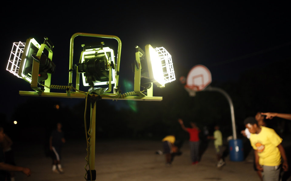 Photo -  Shop lights glow over the court during midnight basketball at Christ Temple Community Church in Oklahoma City on July 25. Photo by Sarah Phipps, The Oklahoman   SARAH PHIPPS -  SARAH PHIPPS