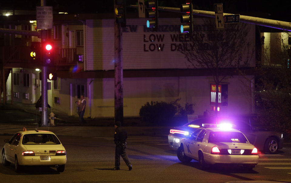 Photo - A Washington State Patrol trooper directs a driver away from a street blocked off several blocks from the scene of an overnight shooting that police said left five people dead, Monday, April 22, 2013, at an apartment complex in Federal Way, Wash. (AP Photo/Ted S. Warren)
