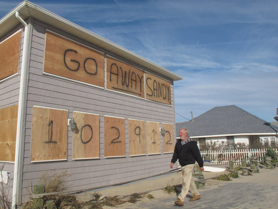 In this Thursday, Nov. 1, 2012 photo, a man walks along the Point Pleasant Beach, N.J. boardwalk, where Superstorm Sandy was an unwelcome visitor . The storm wrecked boardwalks and amusements up and down the 127-mile Jersey shore. (AP Photo/Wayne Parry)