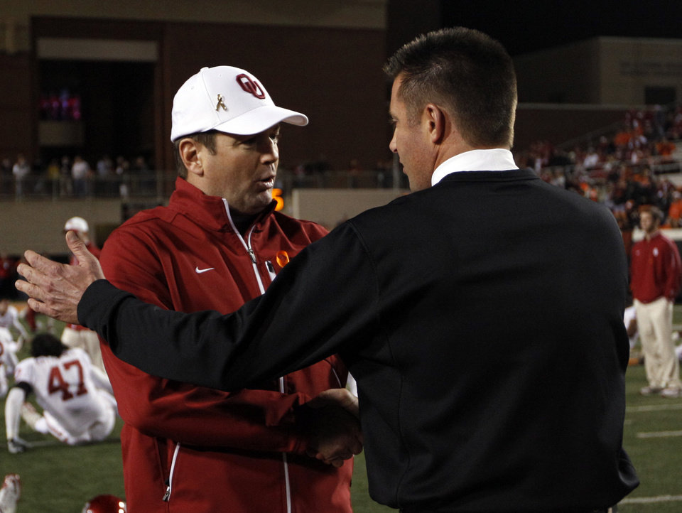 Photo - Oklahoma head coach Bob Stoops and Oklahoma State head coach Mike Gundy greet each other before the Bedlam college football game between the Oklahoma State University Cowboys (OSU) and the University of Oklahoma Sooners (OU) at Boone Pickens Stadium in Stillwater, Okla., Saturday, Dec. 3, 2011. Photo by Sarah Phipps, The Oklahoman
