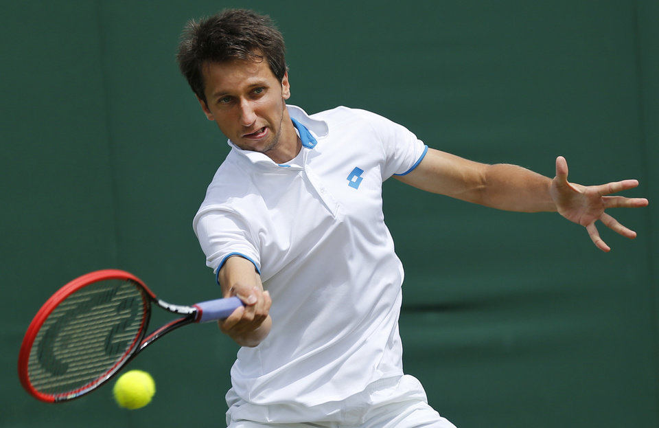 Photo - Sergiy Stakhovsky of Ukraine plays a return to Ernests Gulbis of Latvia during their men's single match at the All England Lawn Tennis Championships in Wimbledon, London,  Wednesday, June  25, 2014. (AP Photo/Ben Curtis)