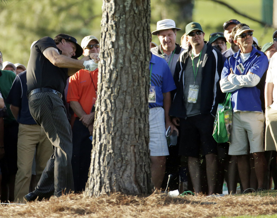 Photo - Phil Mickelson hits from behind a tree off the 17th hole during the first round of the Masters golf tournament Thursday, April 10, 2014, in Augusta, Ga. (AP Photo/Charlie Riedel)