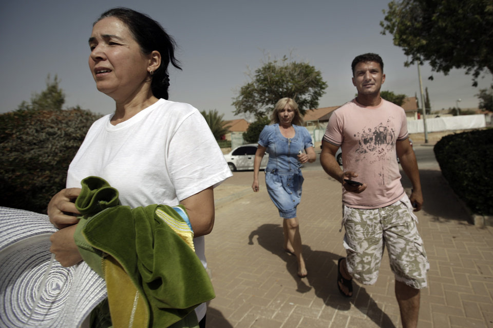 Photo - Israelis run to a shelter as a siren warning of incoming rockets is heard around the southern city of Beersheba, Israel, Saturday, July 12, 2014. Israeli airstrikes overnight targeting Hamas in Gaza hit a mosque its military says concealed the militant group's weapons, in an offensive that showed no signs of slowing down. Israel launched its campaign five days ago to stop relentless rocket fire on its citizens. While there have been no fatalities in Israel, Palestinian officials said overnight attacks raised the death toll there to over 120, with more than 920 wounded. (AP Photo/Tsafrir Abayov)
