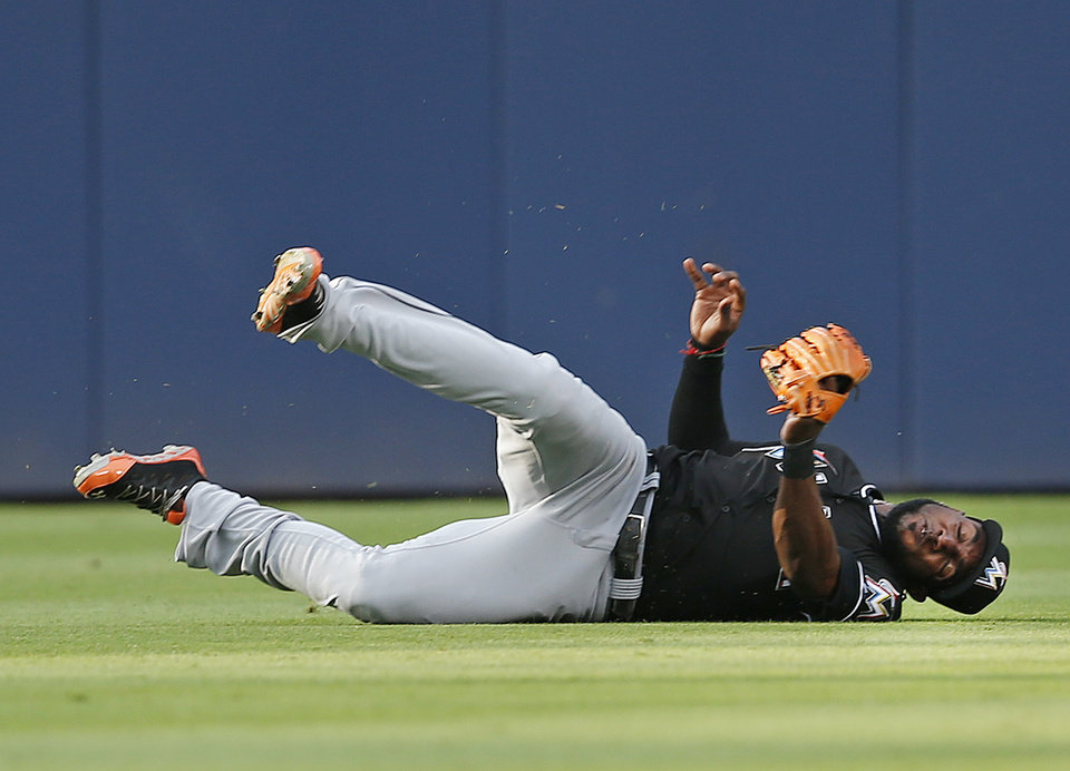 Photo - Miami Marlins center fielder Marcell Ozuna (13) makes a catch to retire Atlanta Braves' Evan Gattis in the second inning of a baseball game, Thursday, July 24, 2014 in Atlanta. (AP Photo)
