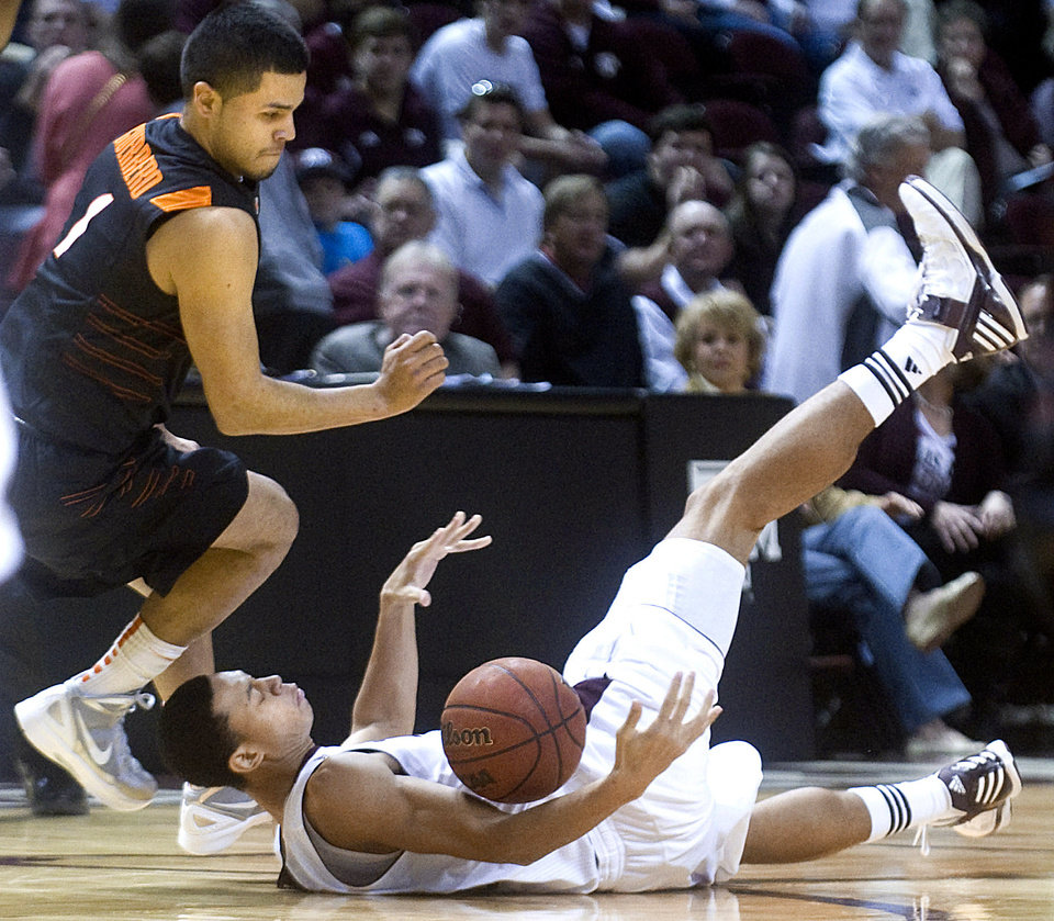 Texas A&M\'s Jordan Green falls to the court after being fouled by Oklahoma State\'s C.J. Guerrero during the first half of an NCAA college basketball game at Reed Arena in College Station, Texas, Saturday, Jan. 28, 2012. (AP Photo/Bryan-College Station Eagle, Stuart Villanueva) ORG XMIT: TXBRY102