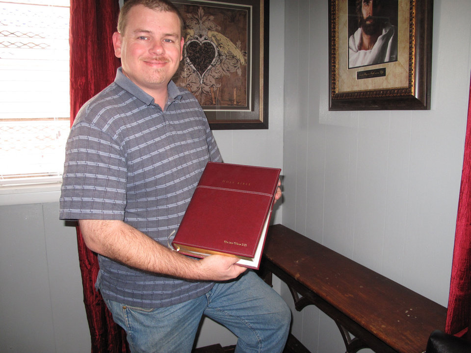 Photo - Rick Denny, executive director of the Jesus House, holds a new engraved Bible presented to the emergency shelter by friends and family of Braylee Rae Henry.  CARLA HINTON - CARLA HINTON