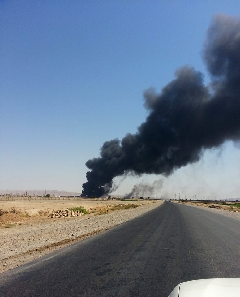 Photo - A column of smoke rises from Beiji oil refinery, some 250 kilometers (155 miles) north of Baghdad, Iraq, Thursday, June 19, 2014. The fighting at Beiji comes as Iraq has asked the U.S. for airstrikes targeting the militants from the Islamic State of Iraq and the Levant. While U.S. President Barack Obama has not fully ruled out the possibility of launching airstrikes, such action is not imminent in part because intelligence agencies have been unable to identify clear targets on the ground, officials said.(AP Photo)