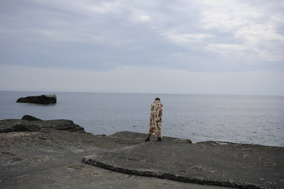 Photo - A Russian tourist  stands on a  Black Sea beach about 35 km. (22 miles) from Yalta, Crimea, Sunday, June 15, 2014. When Russia annexed the Black Sea peninsula of Crimea earlier this year, it regained not only harbors for its navy and abandoned Ukrainian military bases but also long stretches of pebble beaches that were the summer destination of choice for millions of Soviet citizens. The Kremlin is hoping to attract tourists to Crimea, which Russia annexed in March, by asking state-controlled companies to send their employees on free vacation trips.(AP Photo/Andrew Lubimov)