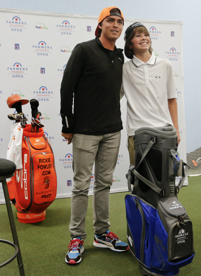 Photo - Former Oklahoma State golfer and current PGA pro Rickie Fowler poses for a photo with Moore High School's Alex McCown while Fowler makes a special appearance at Golfsmith in Oklahoma City, Okla. as a surprise to members for the three Moore school's golf teams, Monday, Jan. 6, 2014.  .Photo by Chris Landsberger, The Oklahoman