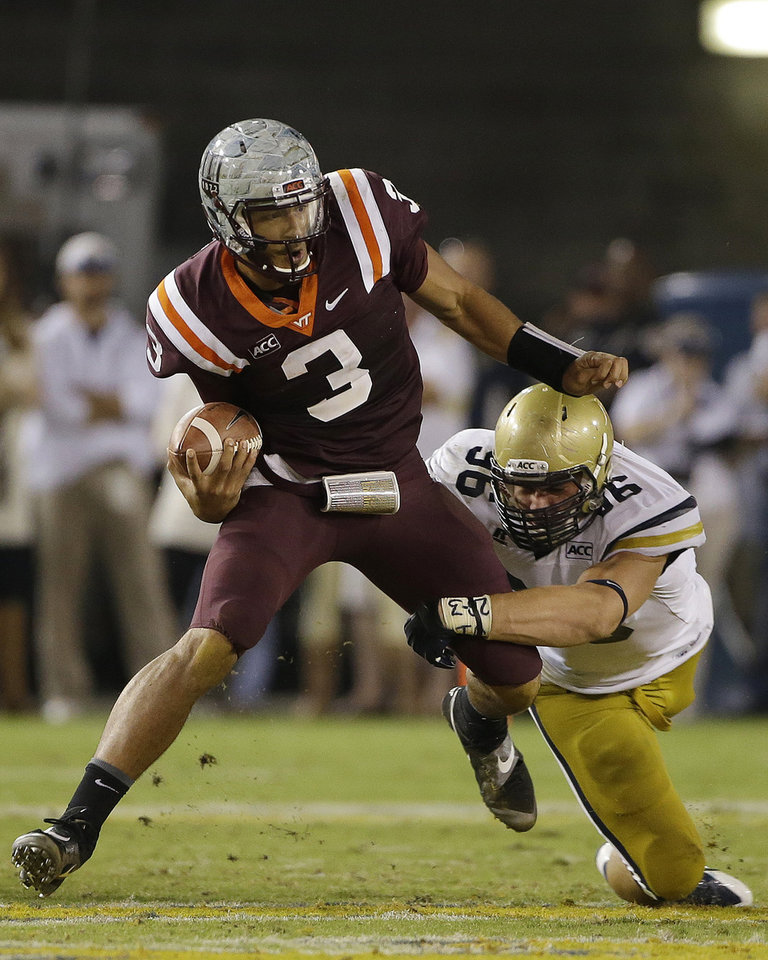 Photo - Virginia Tech quarterback Logan Thomas (3) is brought down by Georgia Tech defensive lineman Adam Gotsis (96) in the second half of an NCAA college football game on Thursday, Sept. 26, 2013, in Atlanta. (AP Photo/John Bazemore)
