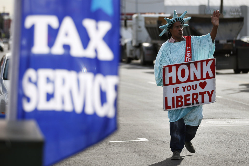 FILE - In this Tuesday, Jan. 22, 2013, file photo, dressed as the Statue of Liberty, part-time employee, Zidkijah Zabad, waves to passing motorists while holding a sign to advertise for Liberty Tax Service in Los Angeles. With tax season in full swing, a newly released poll says an overwhelming majority of adults don't believe it is ever OK to cheat on their income taxes, with most citing personal integrity as the biggest reason why. (AP Photo/Jae C. Hong)