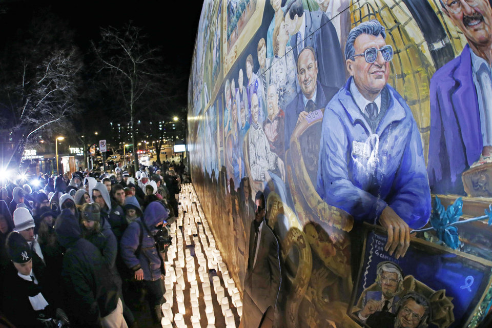 Photo - People gather in front of a mural containing a likeness of former Penn State football coach Joe Paterno, right, at a candlelight memorial on the first anniversary of his death, Tuesday, Jan. 22, 2013, in State College, Pa. (AP Photo/Gene J. Puskar)