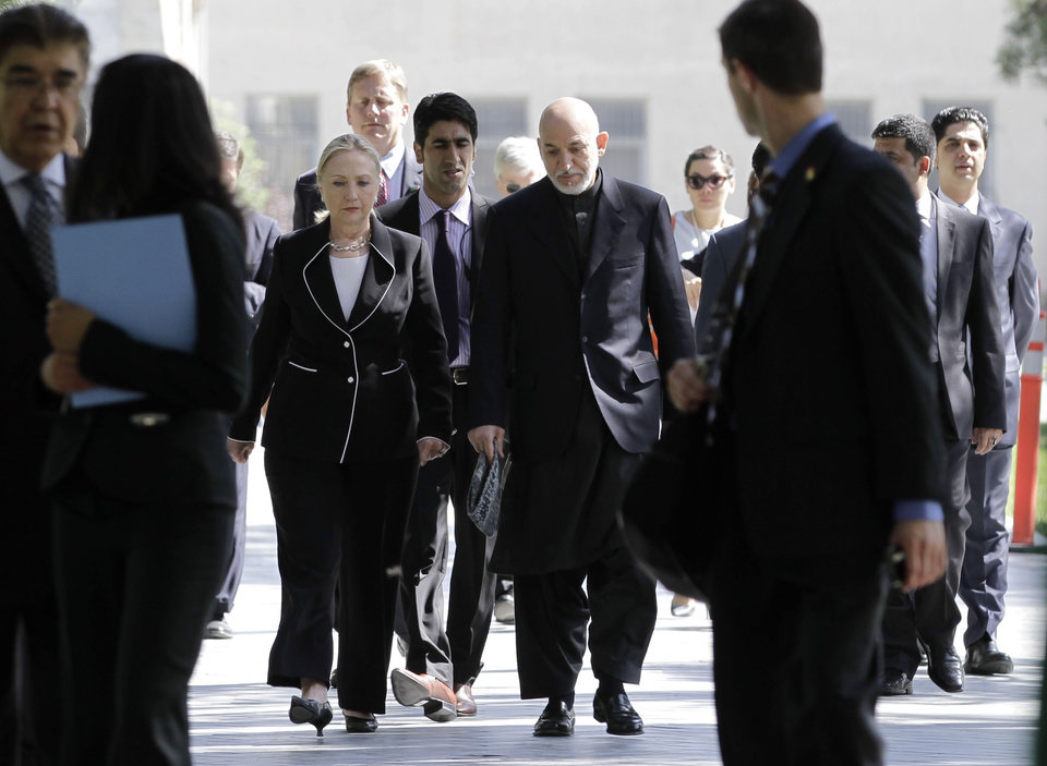 Photo -   Afghan President Hamid Karzai, center right, walks with U.S. Secretary of State Hillary Rodham Clinton center left, as they arrive for a joint press conference at the Presidential Palace in Kabul, Afghanistan, Saturday, July 7, 2012. Clinton announced that President Barack Obama had designated Afghanistan as a