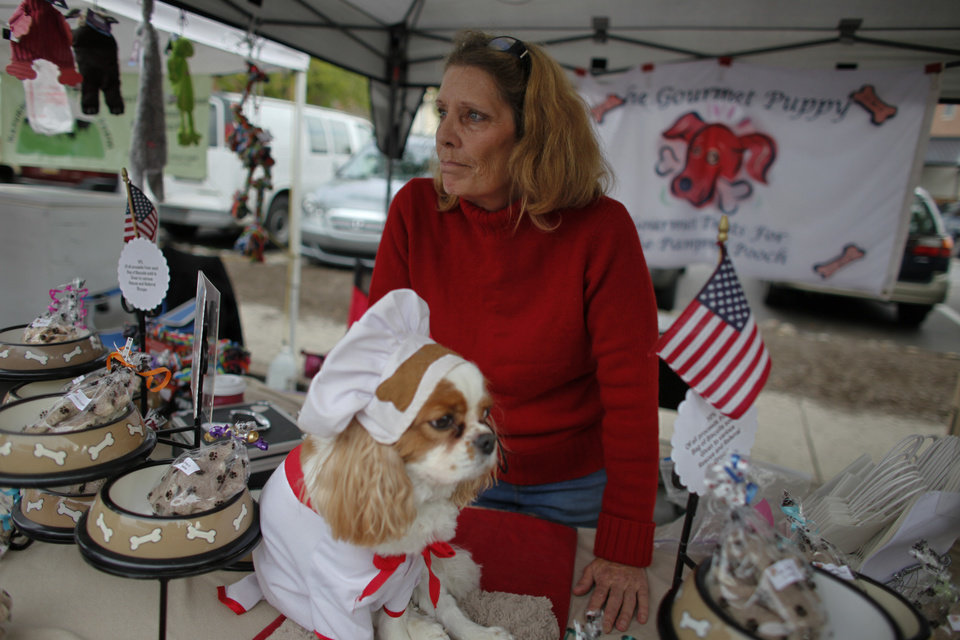 Photo -   Cynthia Kopp and her dog Aires wait for customers at a farmers market, Saturday Oct. 6, 2012, in Doylestown Pa. Kopp, 56, lost her accounting job in the recession and now works part-time as a supermarket cashier and comes to the farmers market each week to sell $5 bags of her gourmet dog biscuits.