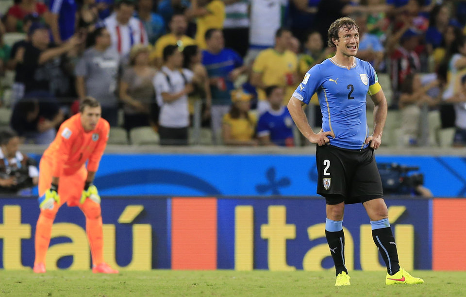 Photo - Uruguay's Diego Lugano reacts after Costa Rica scored their third goal during the group D World Cup soccer match between Uruguay and Costa Rica at the Arena Castelao in Fortaleza, Brazil, Saturday, June 14, 2014.    (AP Photo/Bernat Armangue)