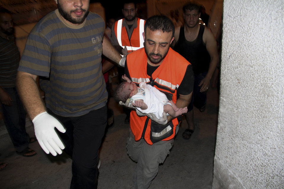 Photo - A Palestinian medic carries a wounded baby, following an Israeli airstrike on a building, at the treatment room of al Najar hospital in Rafah in the southern Gaza Strip, Thursday, Aug. 21, 2014. (AP Photo/Hatem Ali)