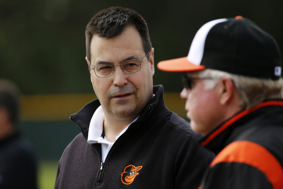 Photo - Baltimore Orioles executive vice president for baseball operations Dan Duquette, left, talks with manager Buck Showalter as they watch a bullpen session on the second day of pitchers and catchers working out at the team's baseball spring training facility in Sarasota, Fla., Saturday, Feb. 15, 2014. The Orioles' first full-squad workout is set for Tuesday. (AP Photo/Gene J. Puskar)