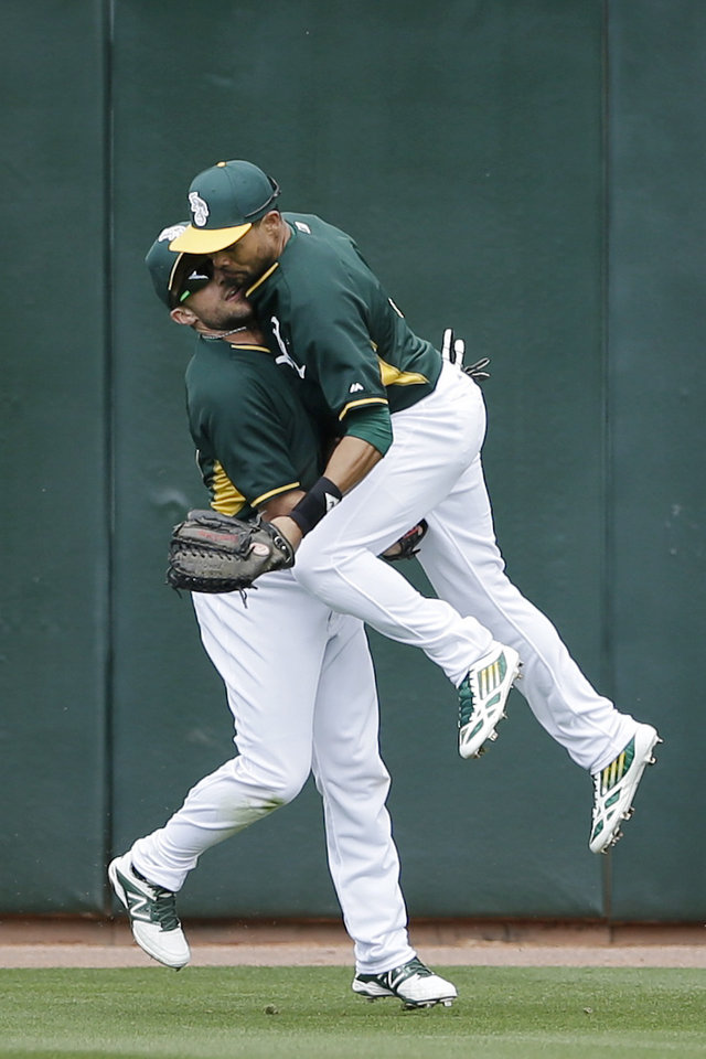 Photo - Oakland Athletics center fielder Coco Crisp, right, collides with left fielder Sam Fuld as he chases down a hit for a double by the Milwaukee Brewers' Jean Segura during the second inning of a spring training baseball game, Thursday, Feb. 27, 2014, in Scottsdale, Ariz. (AP Photo/Gregory Bull)