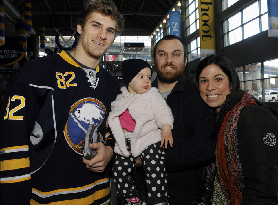 Photo - Buffalo Sabres' Marcus Foligno, poses with Sophia Millanti, and her parents, Matt and Alicia Millanti, as the Sabres greeted their fans before the season debut of an NHL hockey game against the Philadelphia Flyers in Buffalo, N.Y., Sunday, Jan. 20, 2013. (AP Photo/Gary Wiepert)