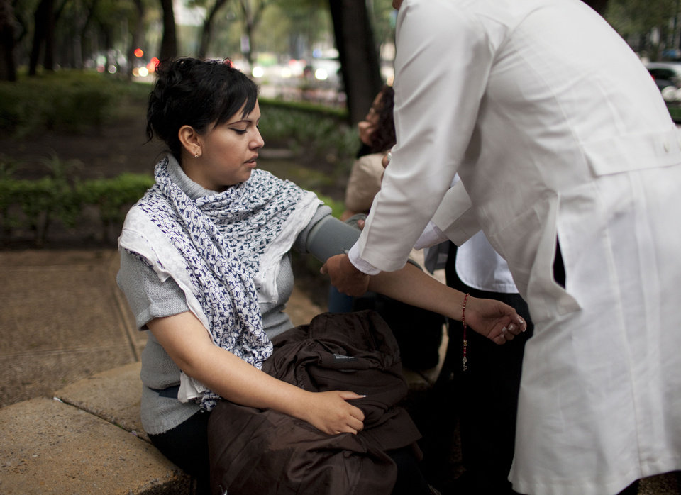 Photo - A woman has her blood pressure checked by a doctor after evacuating her office building due to an earthquake in Mexico City, Wednesday, Aug. 21, 2013. The U.S. Geological Survey said the quake had a magnitude of 6.1 and was centered on the Pacific coast, near the resort of Acapulco. Buildings swayed in the capital and some people evacuated buildings as an earthquake alarm sounded. The alarm also went off for a second, smaller quake a few minutes later. (AP Photo/Ivan Pierre Aguirre)