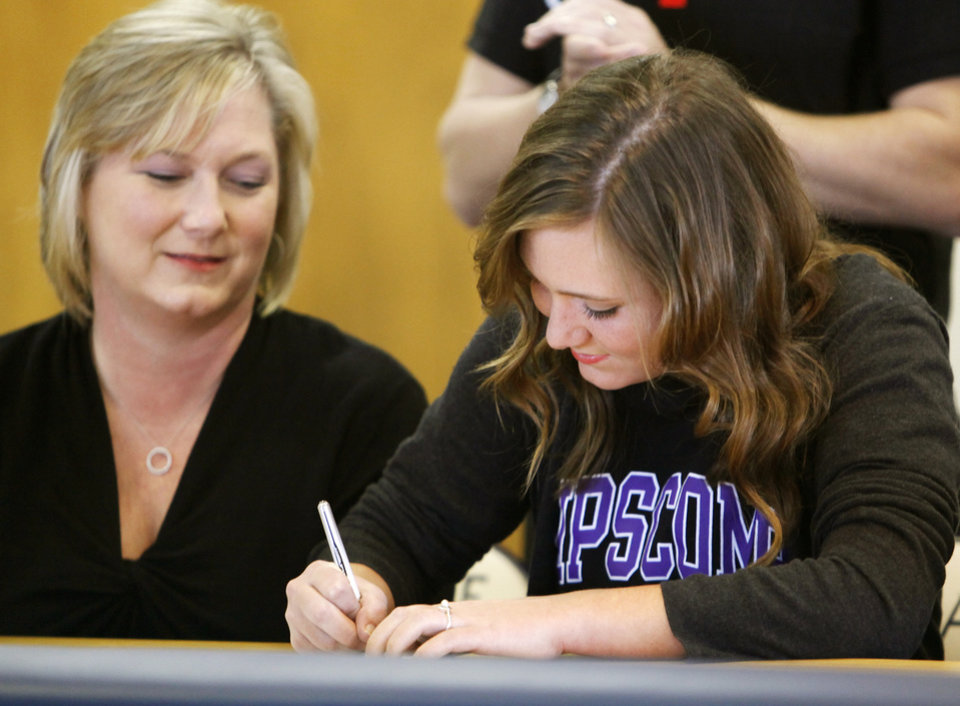 Photo - Heritage Hall's Alex Hickey signs to play soccer at Lipscomb University as her mother, Belinda Hickey, watches during the National Signing Day ceremony at Heritage Hall in Oklahoma City, Wednesday, Feb. 1, 2012. Photo by Nate Billings, The Oklahoman