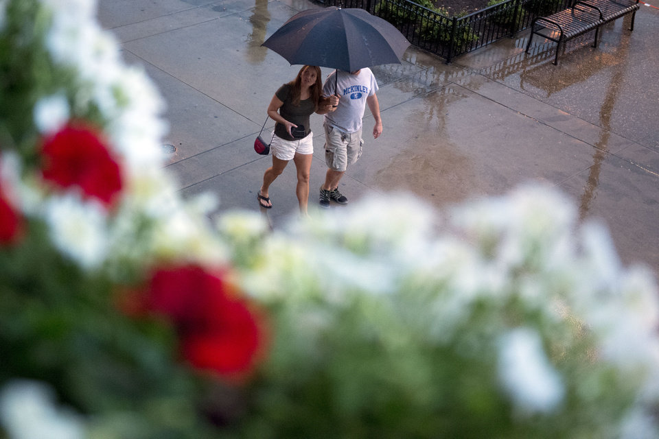 Photo - A couple walks through Market Square as severe weather comes through the area in Knoxville, Tenn., on Sunday, July 27, 2014. Authorities say powerful storms crossing east Tennessee have destroyed 10 homes and damaged others. (AP Photo/The Knoxville News Sentinel, Saul Young)