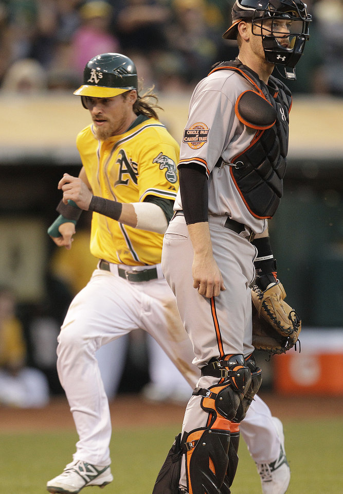 Photo -   Oakland Athletics' Josh Reddick, left, scores behind Baltimore Orioles catcher Matt Wieters in the third inning of a baseball game Saturday, Sept. 15, 2012, in Oakland, Calif. Reddick scored on a double by Chris Carter. (AP Photo/Ben Margot)