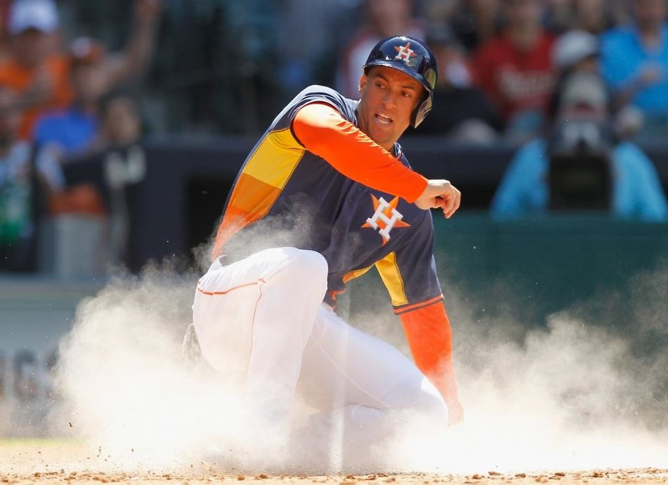 Photo - Houston Astros' George Springer slides safely into home in the seventh inning against Rojos del Aguila de Veracruz's  during a spring exhibition baseball game on Sunday, March 30, 2014, in Houston. Houston won 6-1. (AP Photo/Bob Levey)