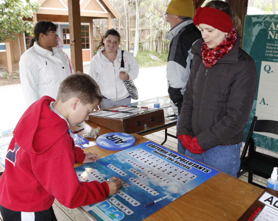 Photo - Below: Melanie Foster, with the Department of Environmental Quality, watches as fourth-grader Cooper Tanner, of Perkins, plays an environmental game during ScienceFest.
