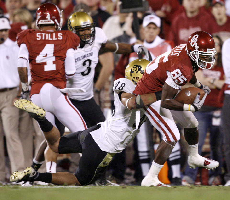Photo - OU's Ryan Broyles fights off Colorado's Liloa Nobriga during the college football game between the University of Oklahoma (OU) Sooners and the University of Colorado Buffaloes at Gaylord Family-Oklahoma Memorial Stadium in Norman, Okla., Saturday, October 30, 2010. Photo by Bryan Terry, The Oklahoman