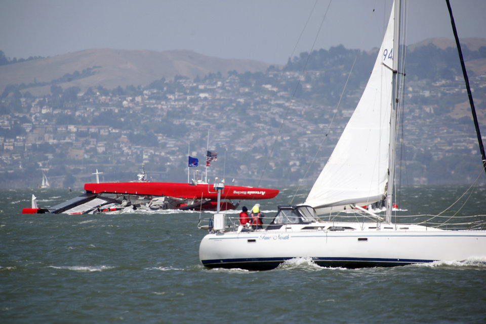 Photo - A sailboat passes the overturned Artemis Racing AC72 catamaran, an America's Cup entry from Sweden, after the boat capsized during training in San Francisco Bay on Thursday, May 9, 2013, in San Francisco, Calif. (AP Photo/San Jose Mercury News, Karl Mondon)  MAGS OUT; NO SALES, MADATORY CREDIT BAY AREA NEWSPAPERS