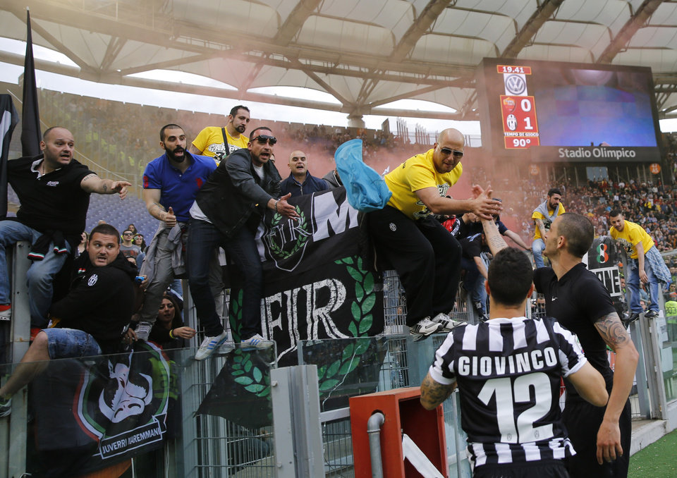 Photo - Juventus players Leonardo Bonucci, right, and Sebastian Giovinco celebrate with supporter at the end of an Italian Serie A soccer match between Roma and Juventus at Rome's Olympic stadium, Sunday, May 11, 2014.   Juventus won 1 - 0. (AP Photo/Alessandra Tarantino)