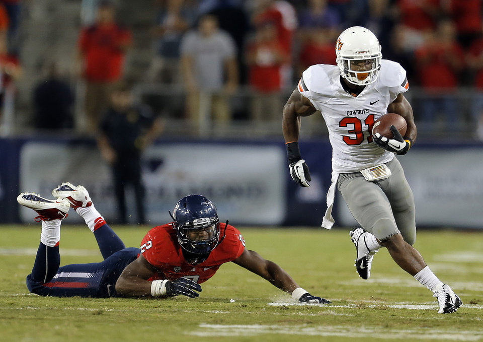 Photo - Oklahoma State's Jeremy Smith (31) gets past Arizona's Marquis Flowers (2) during the college football game between the University  of Arizona and Oklahoma State University at Arizona Stadium in Tucson, Ariz.,  Saturday, Sept. 8, 2012. Photo by Sarah Phipps, The Oklahoman