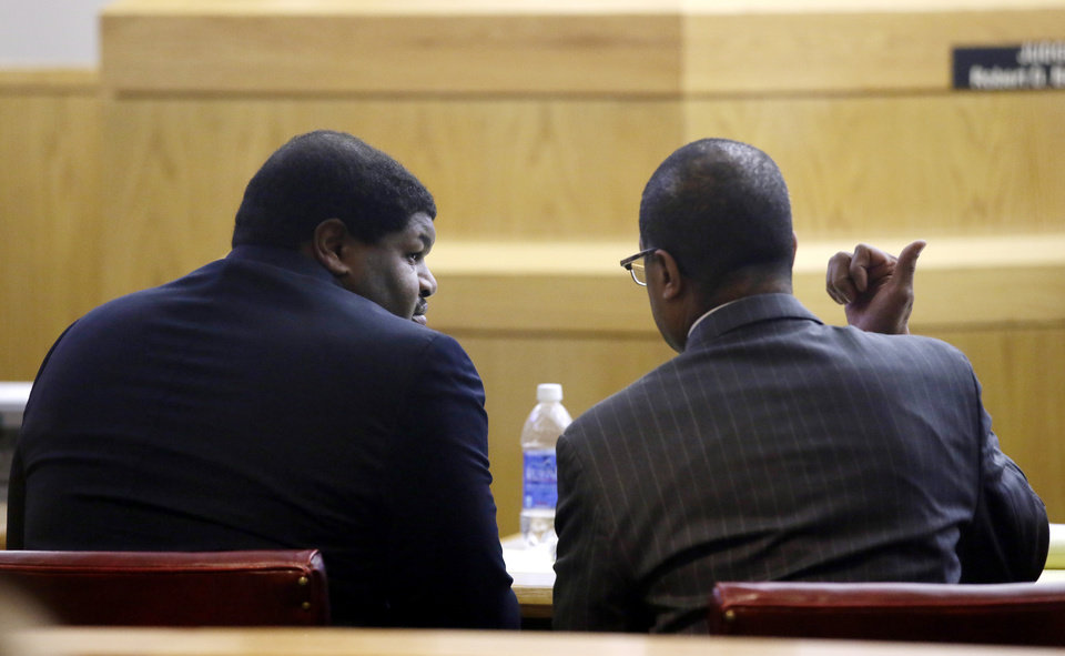 Photo - Former Dallas Cowboy NFL football player Josh Brent talks with a member of is defense team, right,  during his trial for intoxication manslaughter, Friday, Jan. 17, 2014, in Dallas. Brent is accused of driving drunk at the time of a December 2012 crash that killed Cowboys practice squad player Jerry Brown. (AP Photo/Tony Gutierrez)