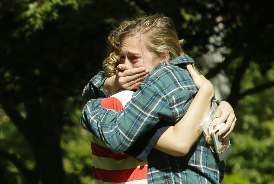 Photo - Two women embrace near a prayer circle on the campus of Seattle Pacific University, Friday, June 6, 2014 in Seattle. Classes were cancelled Friday following a shooting at Otto Miller Hall Thursday afternoon.   A 19-year-old man was fatally shot and two other young people were wounded after a gunman entered the foyer  and started shooting.  Aaron R. Ybarra, 26, was booked into the King County Jail late Thursday for investigation of homicide, according to police and the jail roster. (AP Photo/Ted S. Warren)