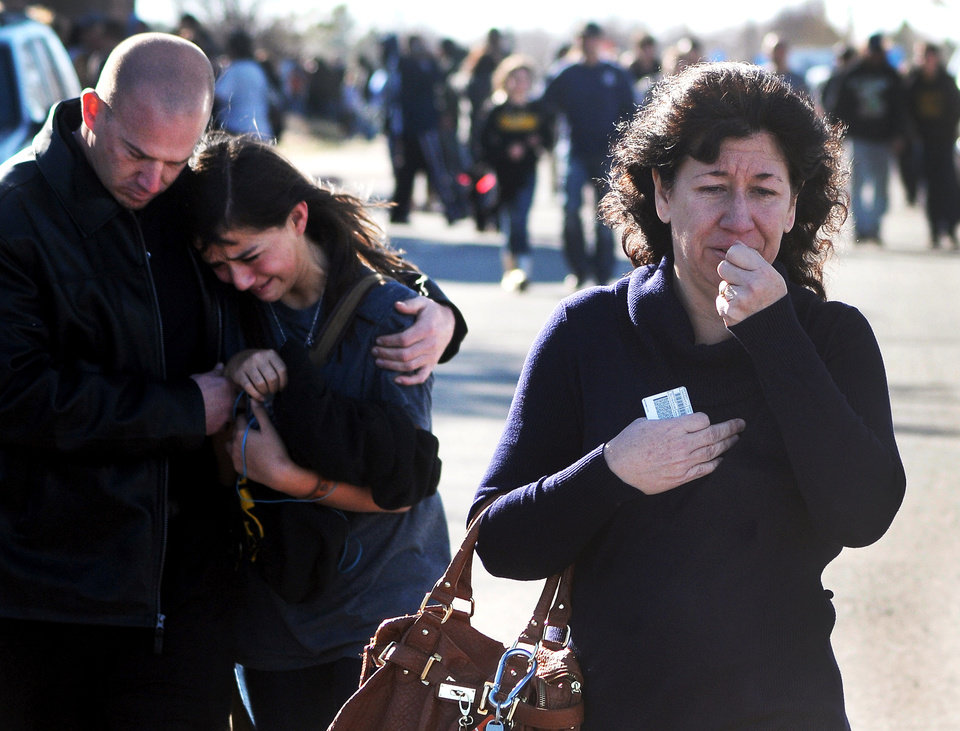 Photo - A woman waits at a staging ground area where families are being reunited with Berrendo Middle School students after a shooting at the school, Tuesday, Jan. 14, 2014, in Roswell, N.M. A shooter opened fire at the middle school, injuring at least two students before being taken into custody. Roswell police said the school was placed on lockdown, and the suspected shooter was arrested. (AP Photo/Roswell Daily Record, Mark Wilson)