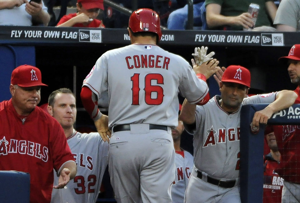 Photo - Los Angeles Angels catcher Hank Conger (16) is congratulated by teammates after scoring on a wild pitch against the Atlanta Braves during the third inning of a baseball game Friday, June 13, 2014, in Atlanta. (AP Photo/David Tulis)