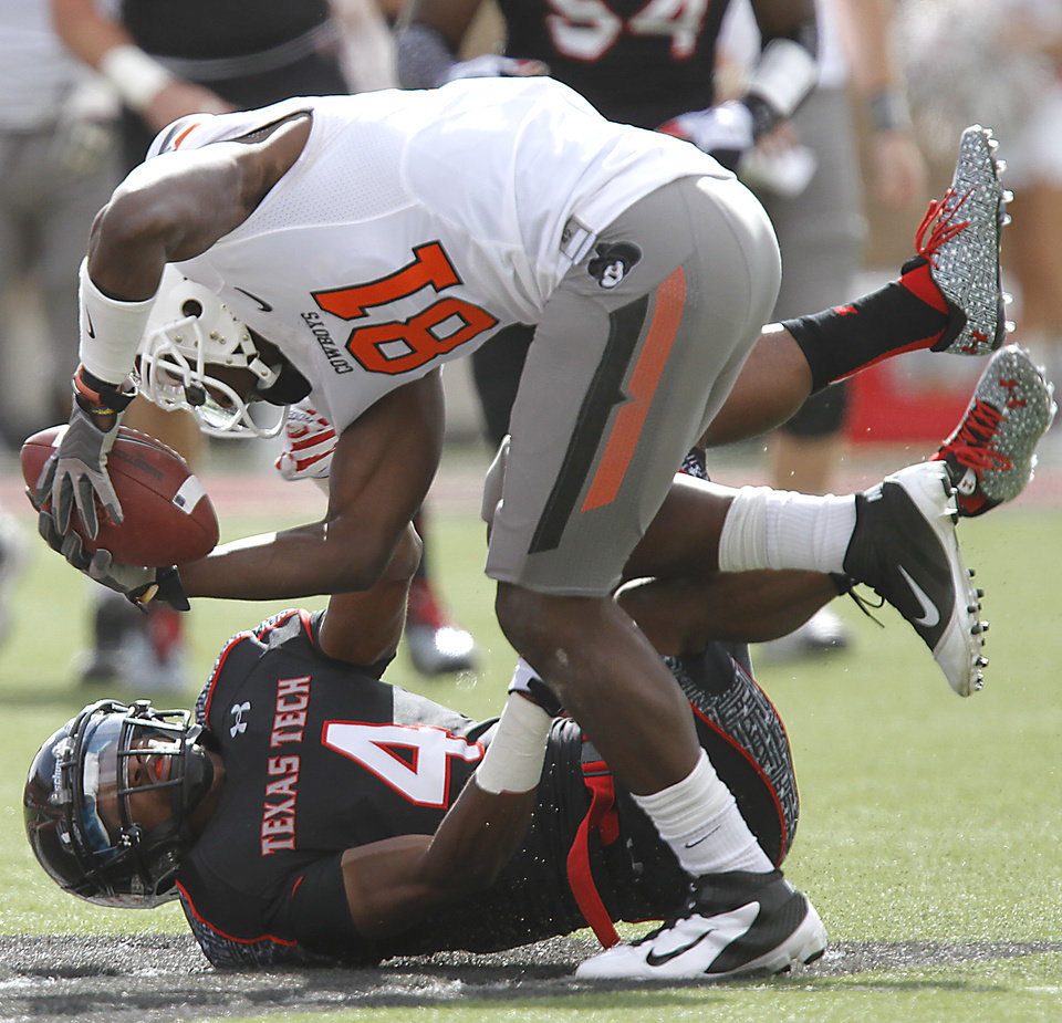 Photo - Oklahoma State Cowboys wide receiver Justin Blackmon (81) is brought down by Texas Tech Red Raiders cornerback Derrick Mays (4) during the college football game between the Oklahoma State University Cowboys (OSU) and Texas Tech University Red Raiders (TTU) at Jones AT&T Stadium on Saturday, Nov. 12, 2011. in Lubbock, Texas.  Photo by Chris Landsberger, The Oklahoman  ORG XMIT: KOD