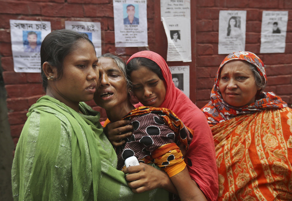 Bangladeshi relatives of missing workers in a building that collapsed on Wednesday comfort each other in Savar, near Dhaka, Bangladesh, Sunday, April 28, 2013. Bangladesh rescuers on Sunday located nine people alive inside the rubble of the multi-story building, as authorities announced they will now use heavy equipment to drill a central hole from the top to look for survivors and dead bodies. (AP Photo/Kevin Frayer)