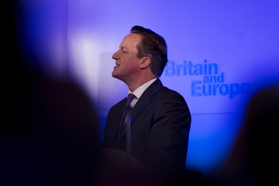 Photo - Britain's Prime Minister David Cameron is seen through an autocue and framed by people in the audience as he makes a speech on having a referendum on staying in the European Union in London, Wednesday, Jan. 23, 2013. Cameron said Wednesday he will offer British citizens a vote on whether to leave the European Union if his party wins the next election, a move which could trigger alarm among fellow member states. (AP Photo/Matt Dunham)
